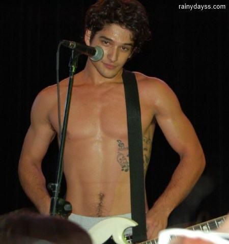 Tyler Posey sem camisa tocando guitarra